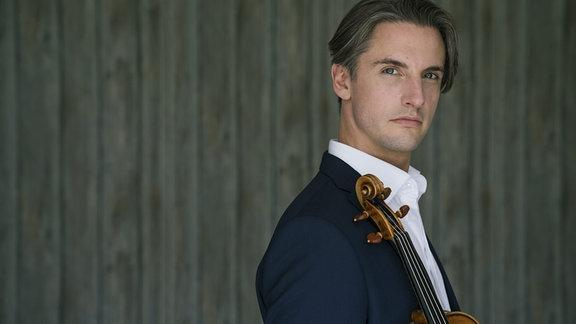Mann mit dunkelblonden, Ohr-langen Haaren sowie Sakko und Hemd blickt über die rechte Schulter in die Kamera; Geige lehnt aufrecht an Schulter