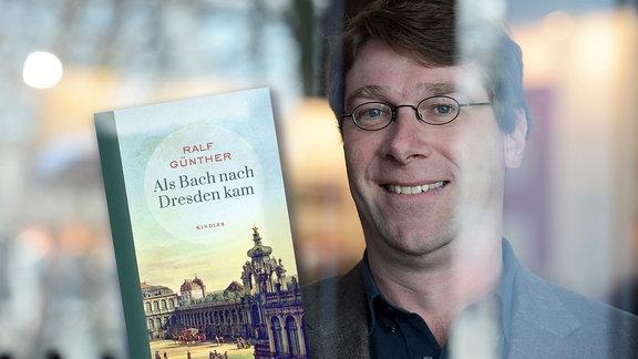 """Der Schriftsteller Ralf Günther im Porträt mit viel Tiefenunschärfe im Vordergrund, daneben montiert das Buchcover zu """"Als Bach nach Dresden kam"""""""