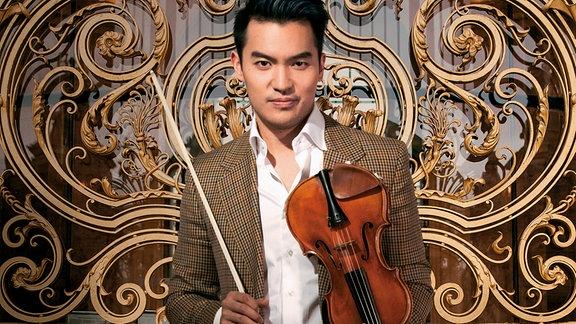 Ray Chen: Junger Mann vor einem goldenen Ornament, mittig, direkt in die Kamera blickend, mit beige kariertem Sakko und weißem Hand und Geige in der Hand.