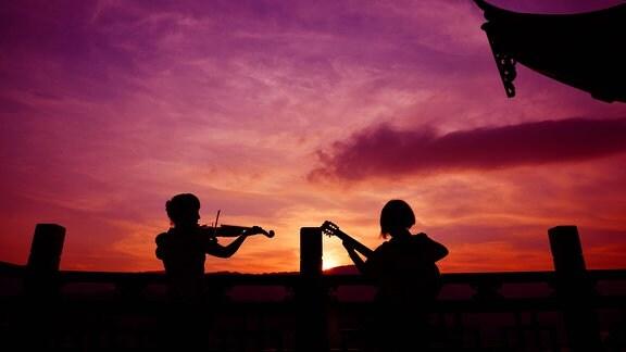 Menschen spielen Instrumente in der Dämmerung