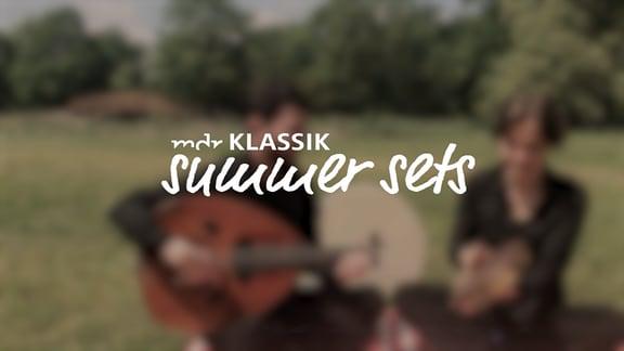 Logo MDR KLASSIK Summer Sets, unscharf im Hintergrund zwei Musiker auf einer Picknickdecke