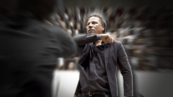 Dirigent Kristjan Järvi dirigiert, um ihn herum aus der Mitte des Bildes Bewegungsunschärfe