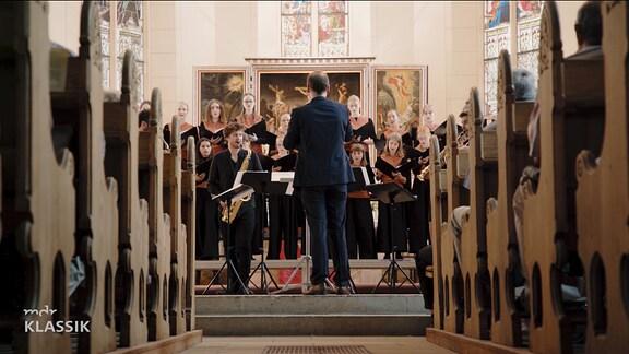Durch Kirchenbänke hindurch sieht man den Leiter des Kinderchors vor dem Chor stehend. Die Kirche warm beleuchtet.