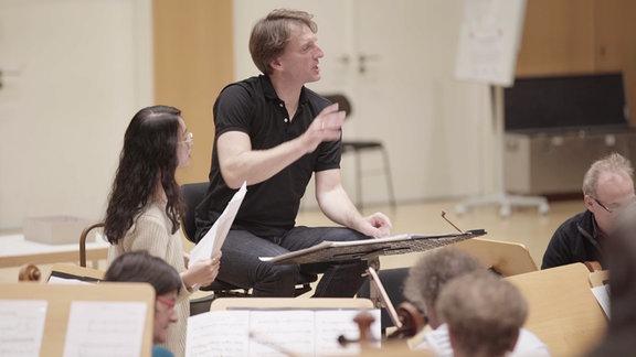Orchesterperspektive: Ulrich Kern (Mann mit etwas längeren blonden Haaren und dunklem Poloshirt) sitzt vor dem Orchester, gestikuliert, neben ihm eine Musikstudentin mit dunklen, langen Haaren, runder Brille, weißem Oberteil und Notenblättern, im Vordergrund das Orchester (tiefenunscharf)