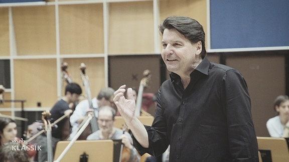 Momentaufnahme aus der Probe: Mann mit schwarzer Kleidung und schwarzen, etwas längeren Haaren steht vor dem Orchester (im Hintergrund, unscharf) und erklärt gestikulierend.