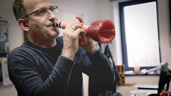 Ein Mann mit Brille und kurzen Haaren bläst in eine Klarinette, die aus klassischem Mundstück, einer Karotte und einer aufgeschnittenen Paprika als Schalltrichter vesteht. Hintergrund leicht unscharf.