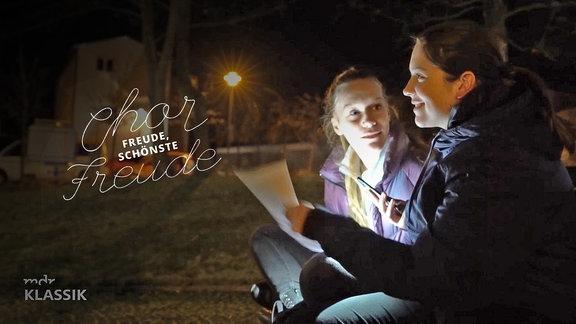 """Bild von zwei Mädchen, die in Dunkelheit rechts im Bild vor Noten mit der Handytaschenlampe sitzen und Singen üben. Im Hintergrund nächtlich beleuchtete Gebäude. Unten links MDR KLASSIK-Logo. Links im Bild Schriftzug """"Chorfreude, schönste Freude"""", Chor und Freude sind in geschwungener Schrift dargestellt."""