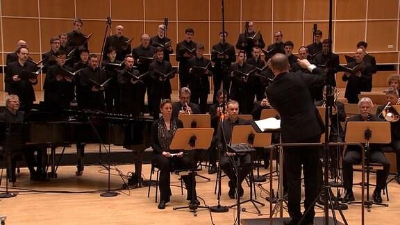 Im Orchesterprobensaal des MDR befindet der MDR-Rundfunkchor, ein Teil des MDR-Sinfonieorchester sowie mit dem Rücken zum Betrachter Dirigent Philipp Ahmann. Schwarze Kleidung. Raum mit Holzwänden.