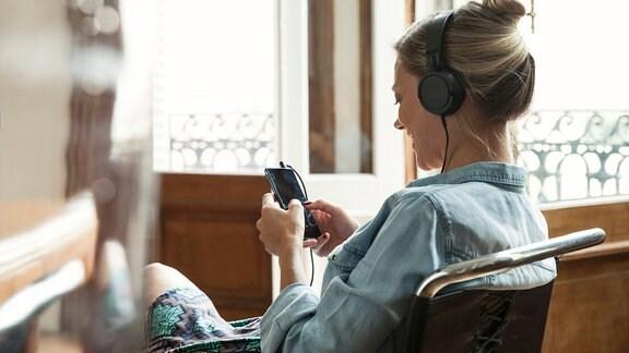 Eine Frau sitzt mit Smartphone und Kopfhörer auf einem Sessel