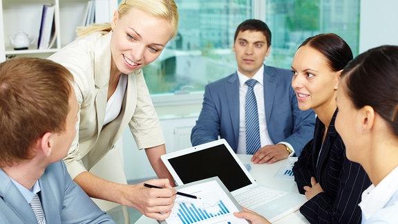 Frauen und Männer diskutieren über eine Grafik