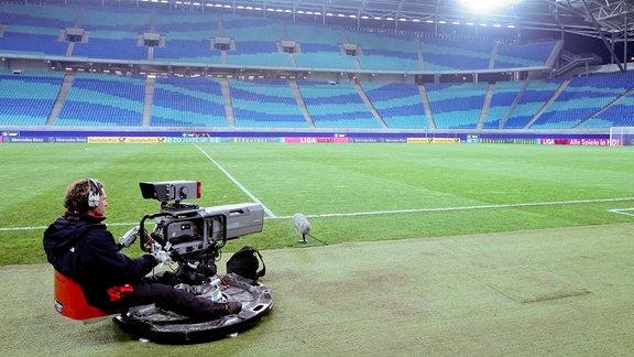Ein Kameramann sitzt hinter seiner TV-Kamera in einem leeren Fußballstadion.