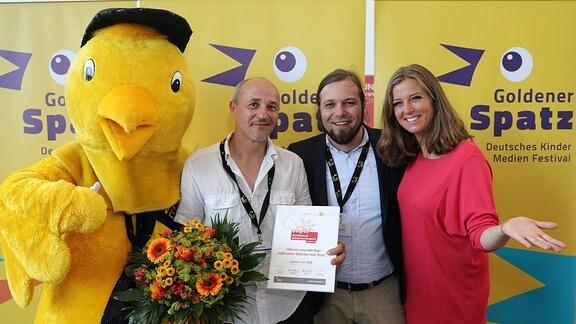 Zwei Männer und eine Frau stehen neben einem großen gelben Plüschspatzen