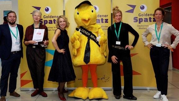 Vier Frauen und ein Mann stehen um das gelbe Plüsch-Maskottchen des Kinderfilmfestivals Golder Spatz.