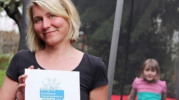 Eine lächelnde blonde Frau hält eine Urkunde vor sich. Im Hingtergrund sitzt ein Kind.