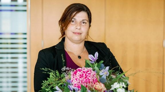 Susanna Erbring hält einen Strauß Blumen in der Hand