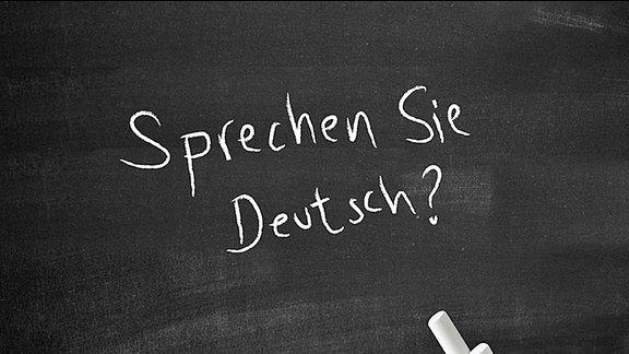 """""""Sprechen Sie deutsch"""" steht auf einer Tafel"""
