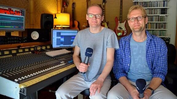 Zwei Männer mit Mikrofonen sitzen nebeneinander in Musikstudio