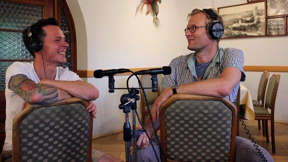 Zwei Männer mit Kopfhörern sitzen verkehrtherum auf Stühlen bei einem Interview