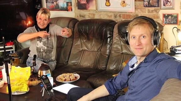 Heike Huth und Tobias Kluge bei Interview mit Kaffe und Kuchen auf einer Couch