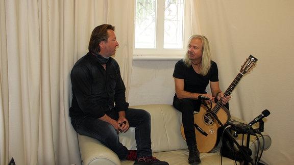 Zwei Männer sitzen auf einer Couchlehne, einer hält eine Gitarre in der Hand