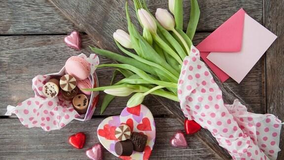 Herzschachtel mit Schokolade, Tulpen und ein Brief