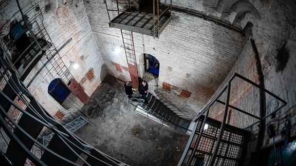 Blick von oben in Inneres eines Turmes, unten stehen zwei Männer