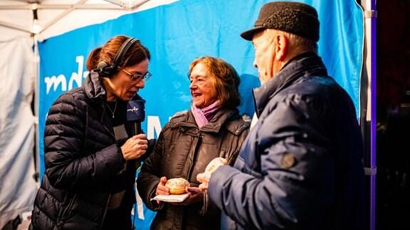 Moderatorin Antonia Kaloff im Interview mit älterem Paar mit Pfannkuchen in der Hand