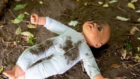 Themenbild: Kindesmisshandlung - Eine Puppe liegt im Schmutz auf dem Boden.