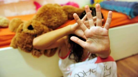 Ein junges Mädchen, vor einem Bett auf dem Boden hockend, hält schützend die Hände vor sich