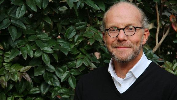 Grauhaariger Mann Bart und Brille vor einer Hecke