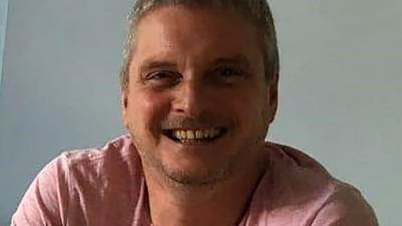 Portrait eines lachenden Mannes in rosa Hemd