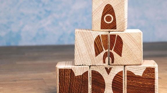 Symbol Bild Start-Up, gestapelte Holzsteine, auf die eine Rakete aufgemalt ist.