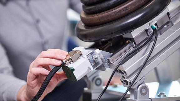 Der smela-Antrieb an eine kleine testanlage angeschlossen, die testet, wie viel Gewicht der Aktuator heben kann. Als Gewichte sieht man runde Hanteln vom Gewichtheben