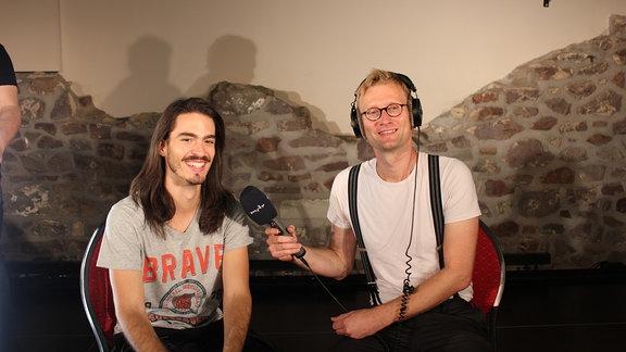Zwei sitzen nebeneinander, einer hält ein Mikrofon.
