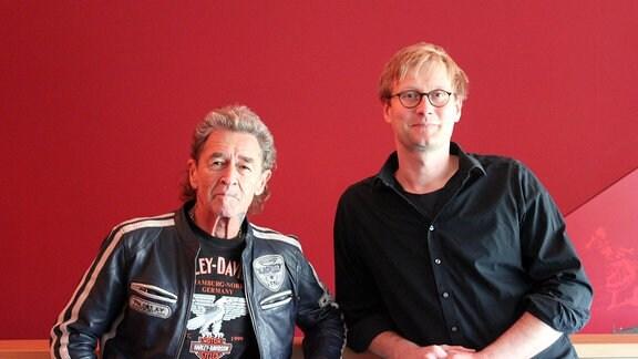 Mann in Lederjacke und Mann mit Brille vor roter Wand