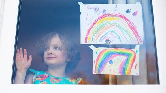 Lara Young neben Regenbogen-Bildern an ihrem Fenster
