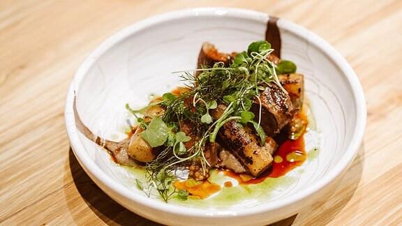 Gericht auf einem weißen Teller – Lammhaxe und Schwarzwurzel.