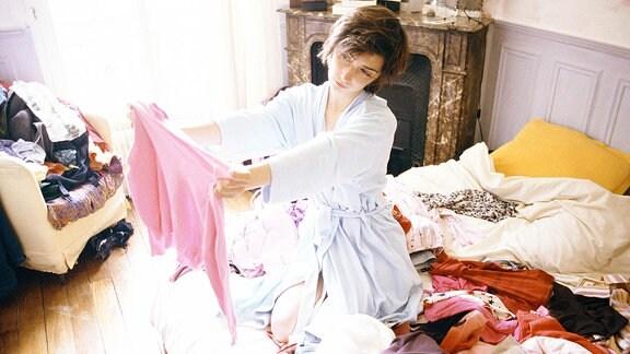 Eine junge Frau hockt auf einem Bett voller Kleidungsstücke und betrachtet ein T-Shirt