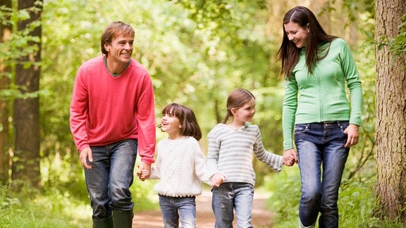 Ein Mann und eine Frau gehen zusammen mit zwei Mädchen durch einen Wald. Alle haben Gummiestiefel an.