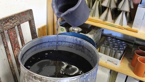 Kerzenwachs wird aus einer Kanne in einen großen Bottich gegossen.