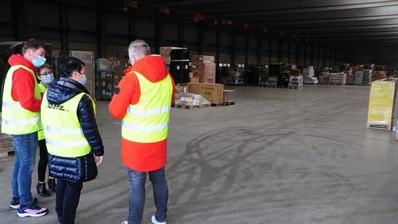Mehrere Personen mit Warnwesten im DHL-Umschlagslager Erfurt