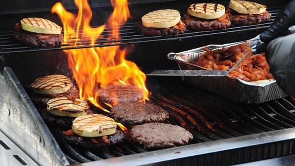 Grillkäse und Burger-Scheiben auf einem Grill