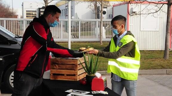 Mann übergibt Gegrilltes an DHL-Mitarbeiter mit Warnweste