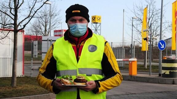 DHL-Mitarbeiter mit Warnweste und gegrilltem Burger