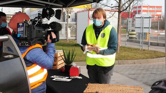 Kameramann filmt Grill mit DHL-Mitarbeiter