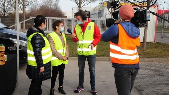 Reporter, Kamerateam und Beschäftigte im DHL-Umschlagslager Erfurt