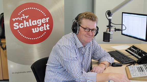 """Radiomoderator Andreas Kallwitz sitzt in einem Hörfunkstudio des MDR-Programms """"MDR Schlagerwelt"""" und hält eine Hand an einen Schieberegler."""