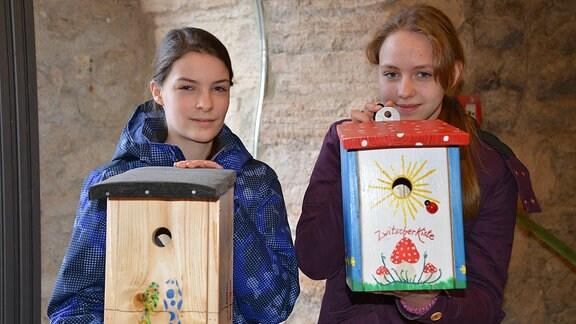 Zwei Mädchen zeigen ihre mit bunten Vögeln und einem Fliegenpilz bemalten Nistkästen