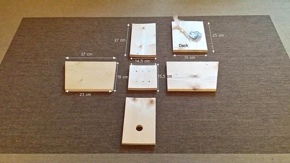 Bausatz Nistkasten: einzelne Bretter liegen auf einem Teppich