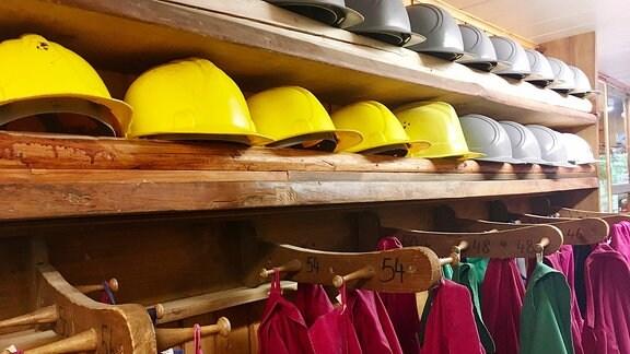 Helme und Jacken in einem Regal im Besucherbergwerk. Man sollte sie auch tatsächlich aufsetzen, denn immer wieder stößt man in der flachen Grube mit dem Kopf an die Steine und es tropft von den Wänden.